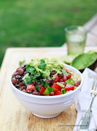 Vegan burrito bowl with quinoa, beans, tomatoes, lettuce, and easy guacamole.