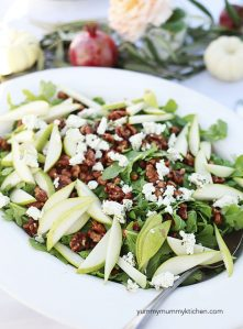 A big beautiful arugula salad with pear slices, candied walnuts, and goat cheese.