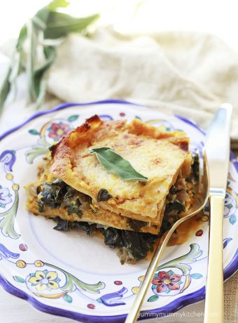 A beautiful slice of pumpkin and chard lasagna topped with a sage leaf.