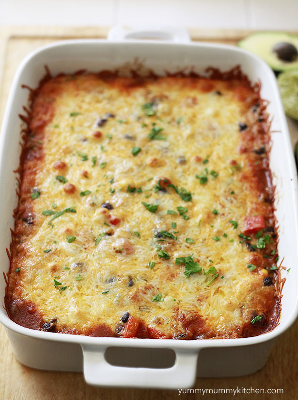 Cheesy baked quinoa enchilada casserole just out of the oven in a white casserole dish.