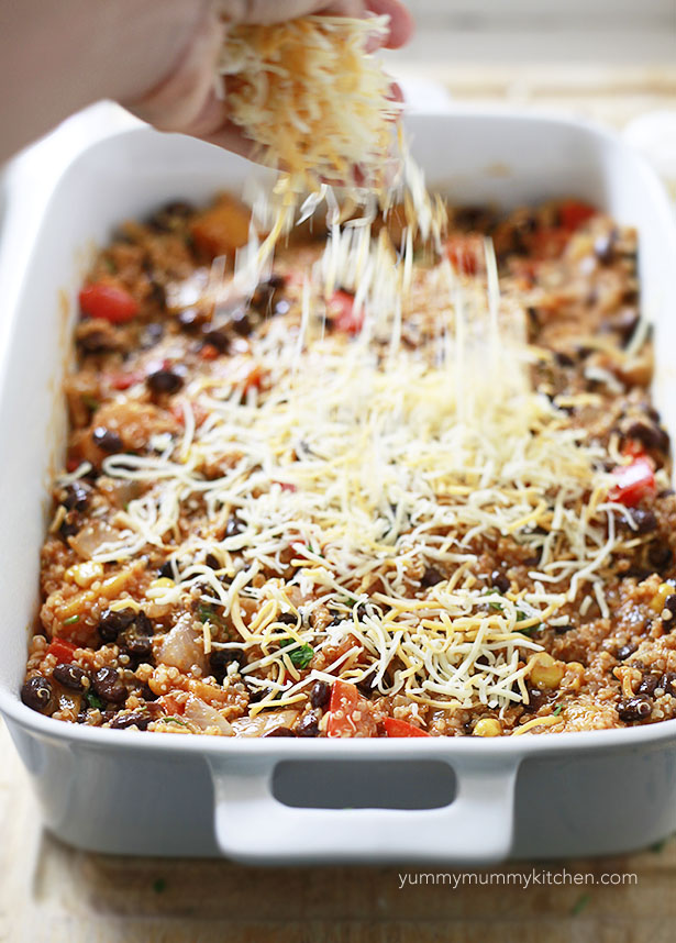 Mexican shredded cheese is sprinkled over the top of a quinoa enchilada bake before it goes into the oven.