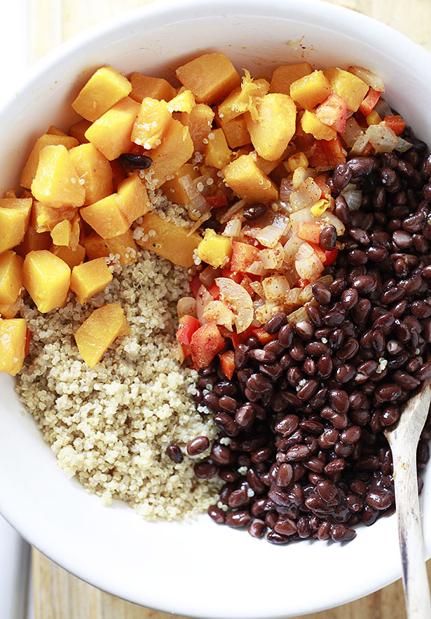 Roasted butternut squash, black beans, quinoa, and an onion pepper mixture in a white bowl about to be mixed together to make a quinoa enchilada bake.