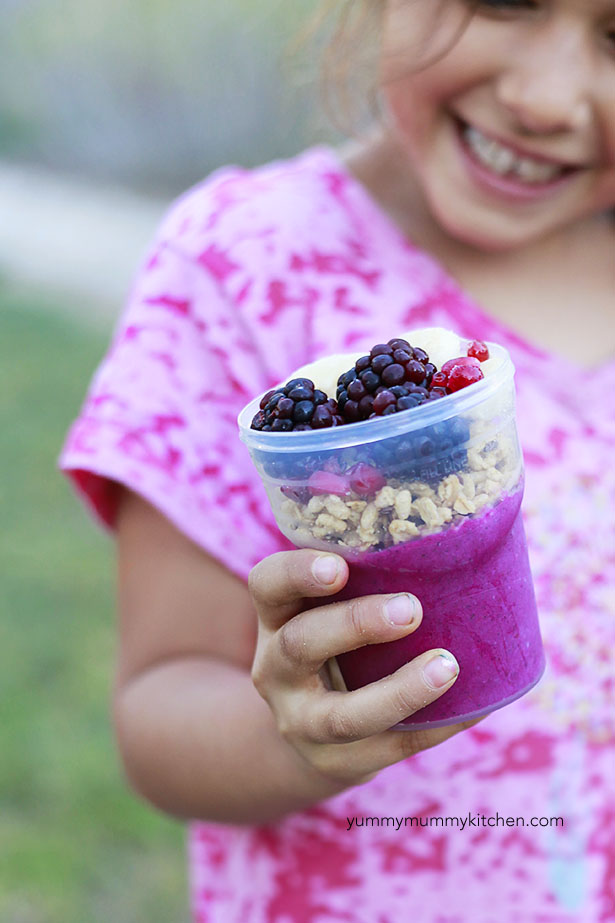 A little girl holds a homemade acai bowl.