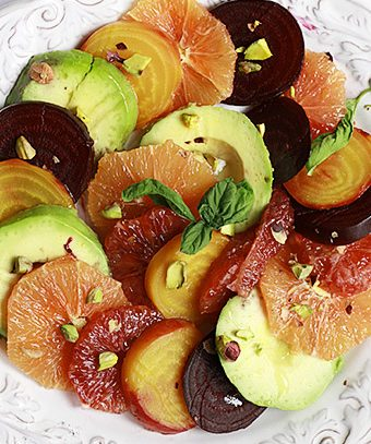 Beautiful roasted beets, avocado, and citrus slices arranged on a plate.