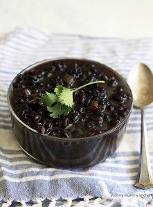 A large bowl of homemade black beans with a sprig of cilantro