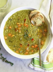 A bowl of vegetarian split pea soup with baguette on the side.
