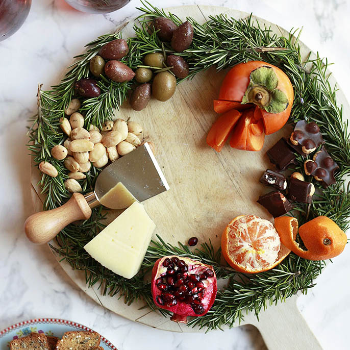 A beautiful holiday wreath cheese board with fruit and nuts.
