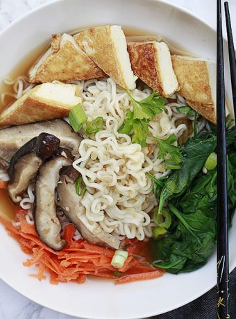 A bowl of vegetarian and vegan ramen with spinach, tofu. mushrooms and carrots.