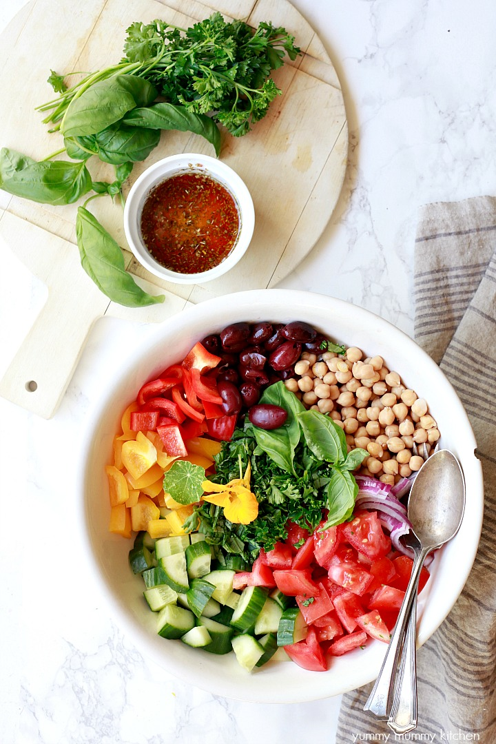 A large white bowl filled with chickpeas, tomatoes, cucumber, bell peppers, olives, and herbs create a vegan Greek salad.