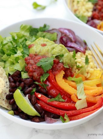 Vegetarian burrito bowl with peppers, black beans, salsa, guacamole, and quinoa.