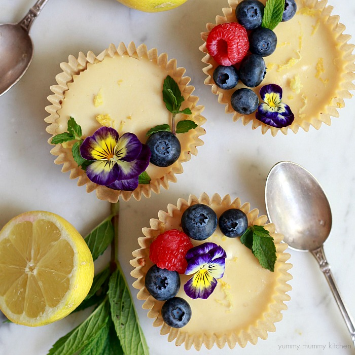 Beautiful lemon tarts topped with berries and edible flowers.