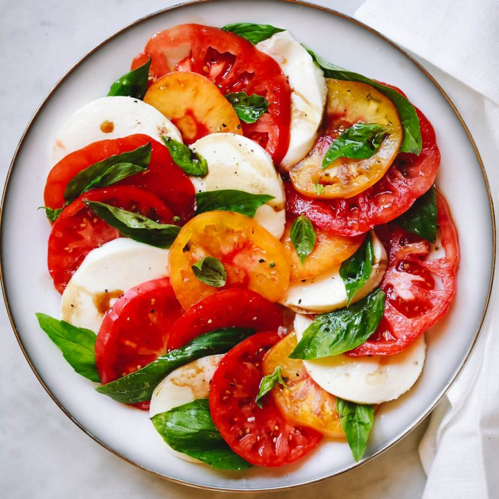 A plate of Caprese salad made with fresh tomatoes, mozzarella, and basil.