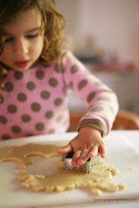 A little girl cutting out sugar cookie dough.