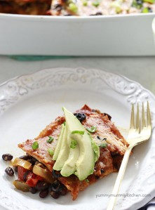 A piece of vegetarian enchilada casserole with avocado on a white plate.