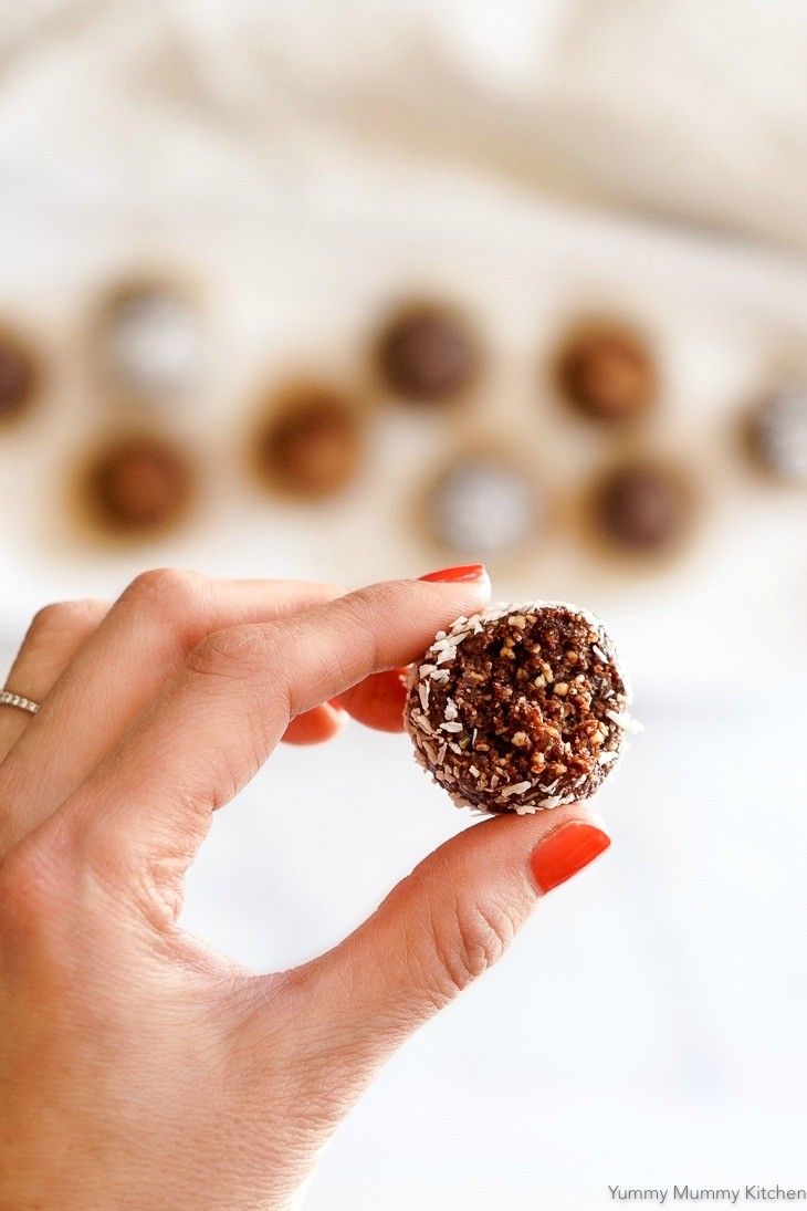 A hand holds one chocolate bliss ball made with dates, cacao and nuts.