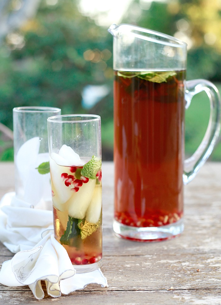 A pitcher and glass of cold brew iced tea with mint and pomegranate on an outdoor table.