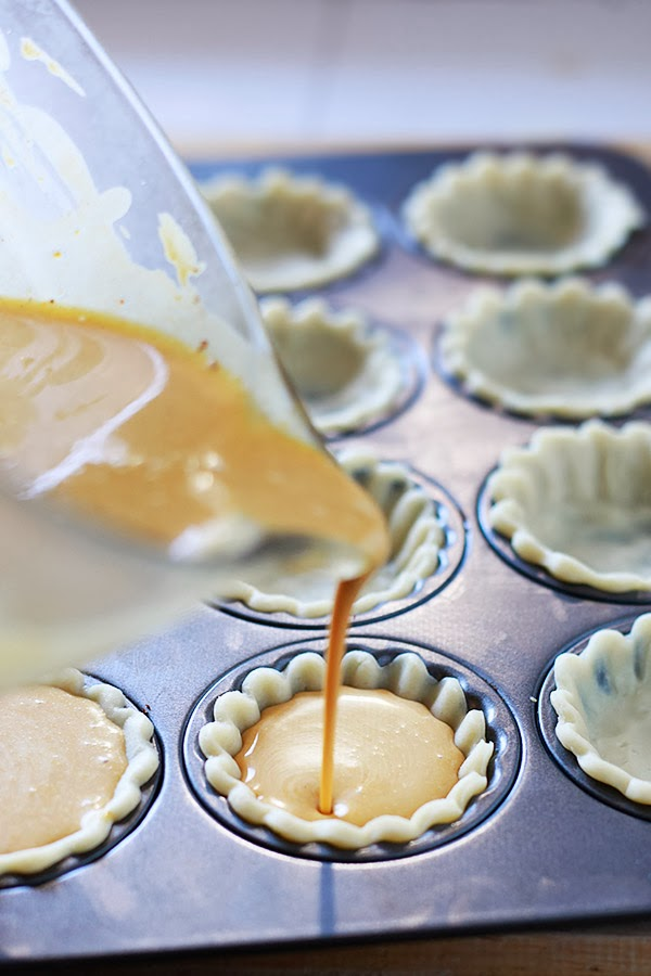 Pumpkin pie filling gets poured into unbaked crusts in a mini tart pan.