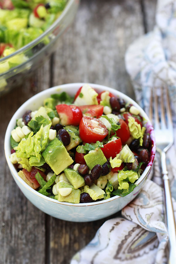 A bowl of Mexican salad with black beans, corn, tomatoes, and Romaine with a delicious light vinaigrette.