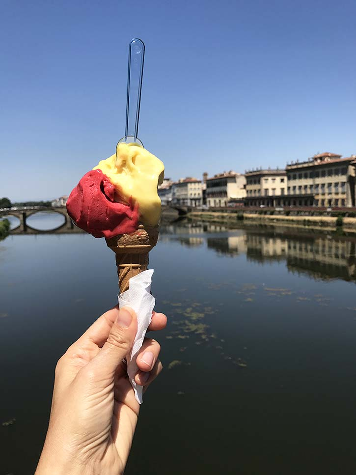 A pretty cone of raspberry and passionfruit gelato in front of the Arno river