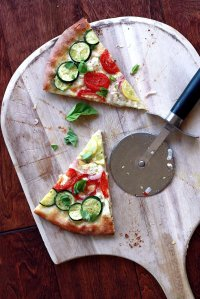 Two slices of vegetable pizza with fresh basil on a pizza peel.