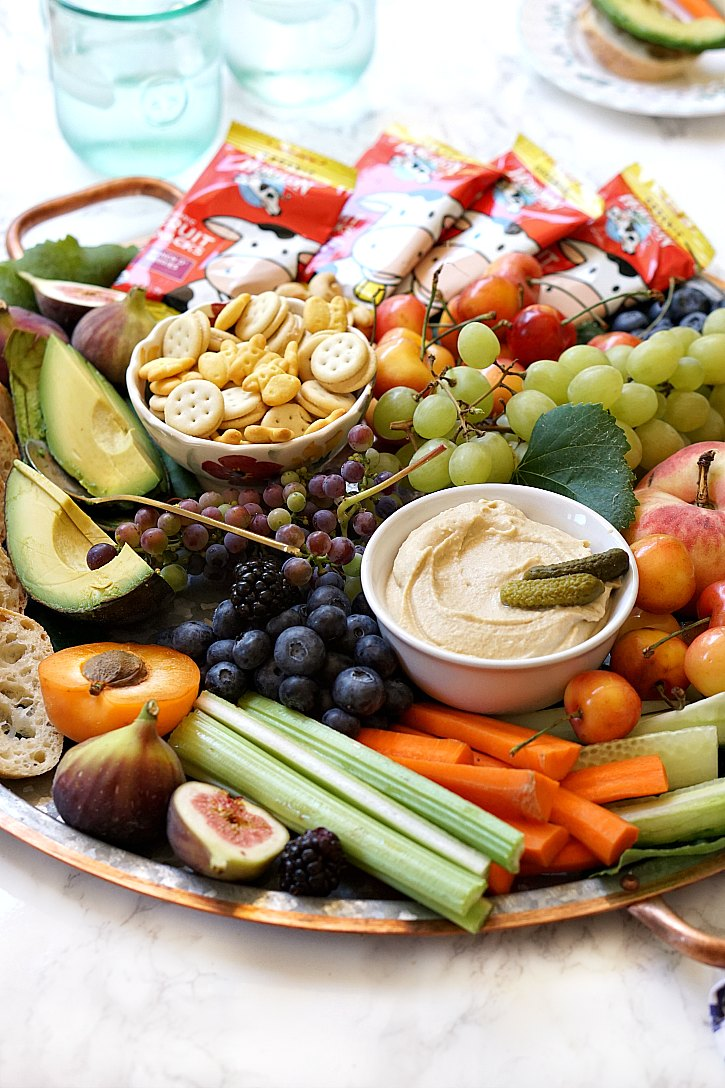 How to make a beautiful kid friendly party platter the whole family will love. Perfect for happy hour or birthday parties, this snack board is loaded with wholesome ingredients like fruit, veggies, nuts, hummus, and kids' snacks.