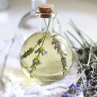 A small glass bottle filled with homemade body oil and lavender.