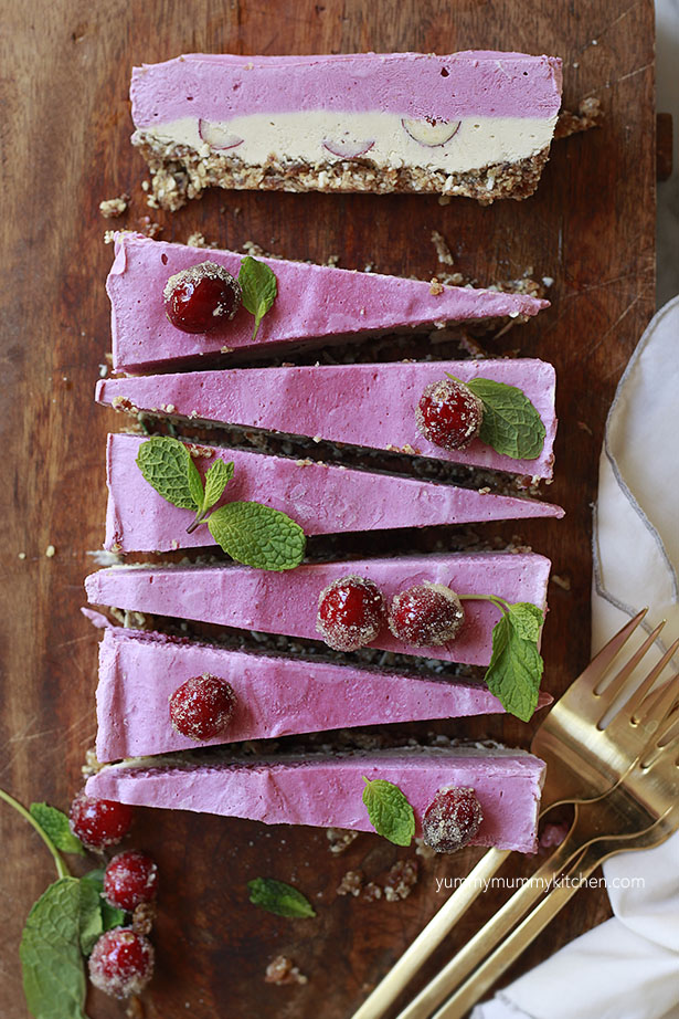 Vegan cranberry cheesecake slices layered with pink and white and a nut date crust.