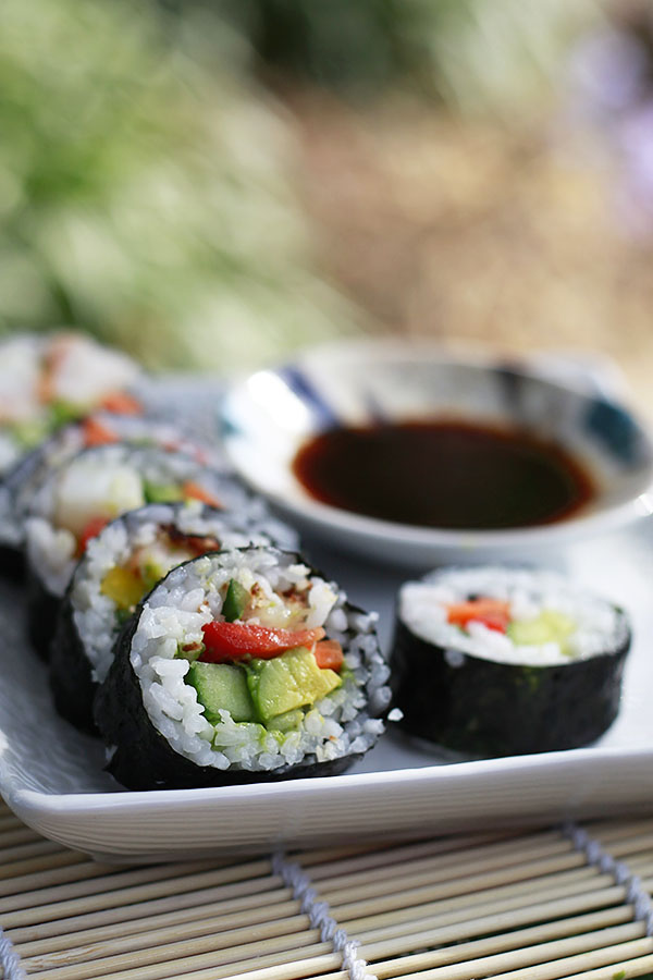 A beautiful photograph of a vegan sushi roll filled with cucumber, avocado, and bell pepper.