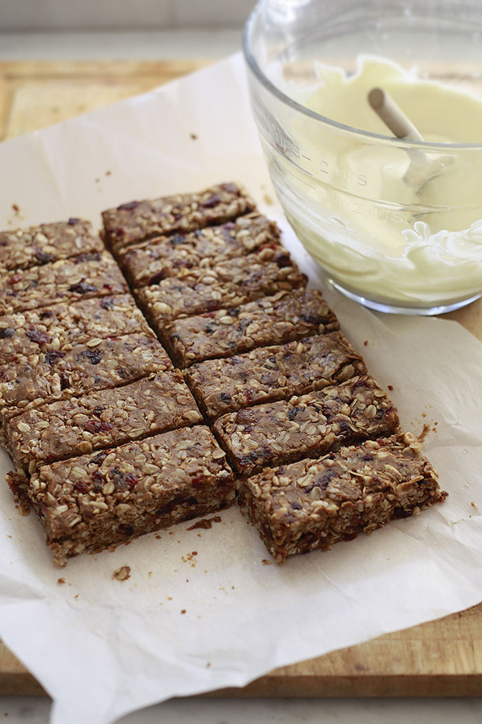 Homemade peanut butter granola bars recipe getting cut into squares on parchment paper.