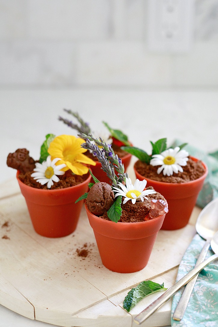 Healthy dirt pudding cups in mini pots with edible flowers.