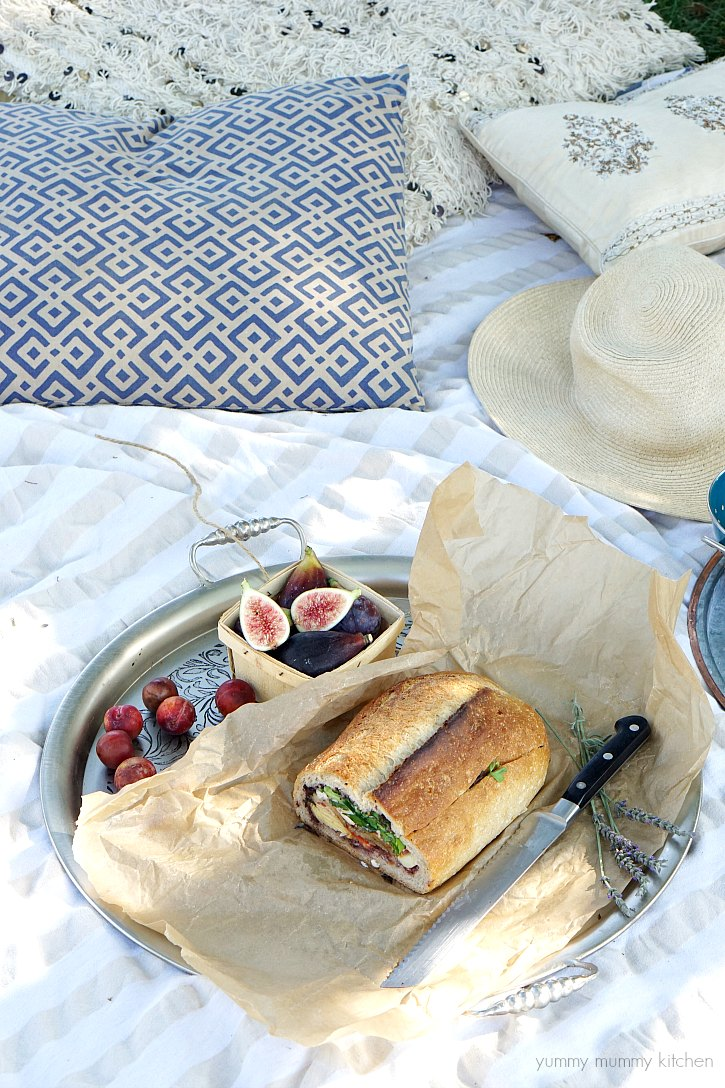 A vegan stuffed muffaletta sandwich with vegetables and tapenade is perfect for a backyard picnic.