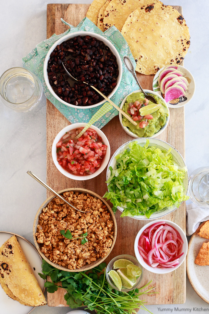 A vegan tempeh taco bar with soft tortillas, black beans, salsa, lettuce, and pickled onions. Tempeh tacos make a great vegan taco dinner.
