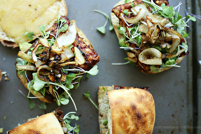 Delicious vegetarian vegan tempeh burgers with bbq sauce on ciabatta buns with caramelized onions and microgreens.