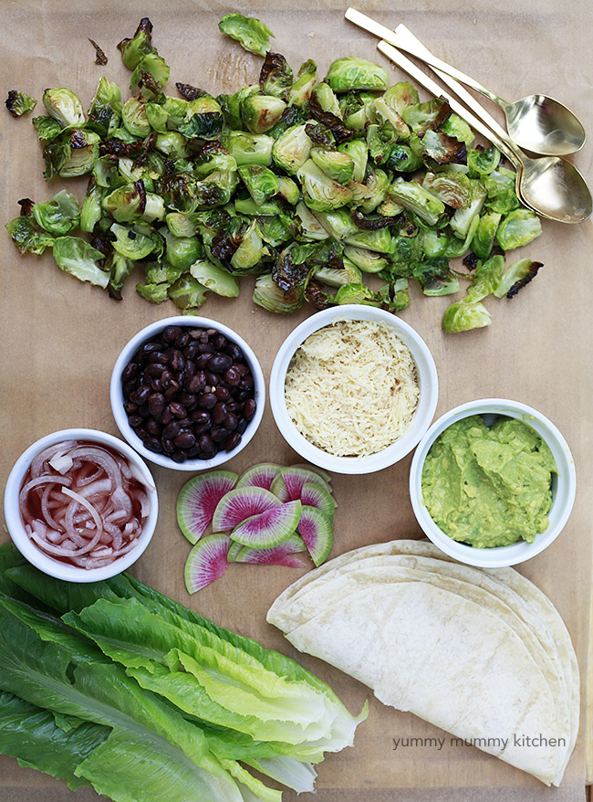 Ingredients for Brussels sprouts tacos include roasted Brussels sprouts, black beans, cheese, guacamole, and pickled onions.