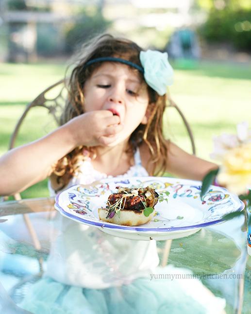 A little girl eats a BBQ tempeh cheeseburger.