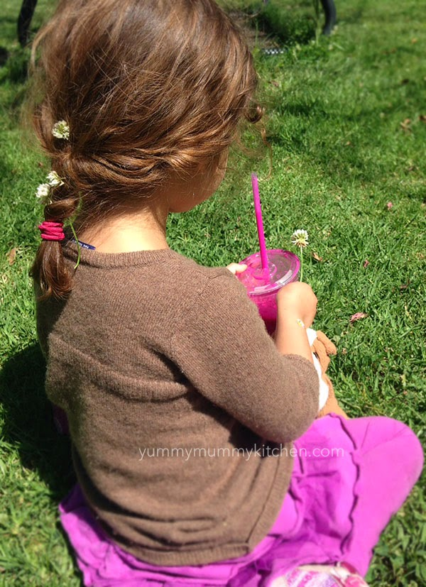 Little girl holding a pink pitaya smoothie.
