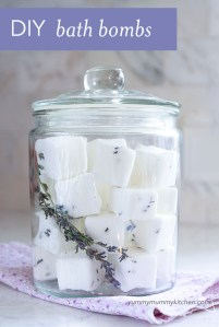 A clear glass canister filled with homemade lavender bath bombs.