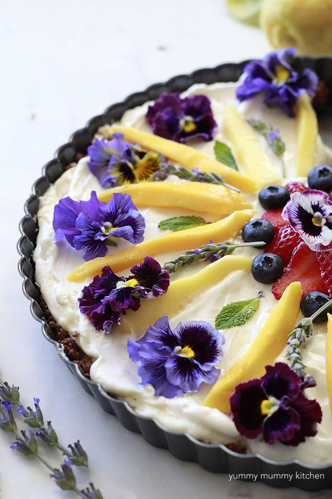 Beautiful fruit and granola tart with edible flowers for breakfast
