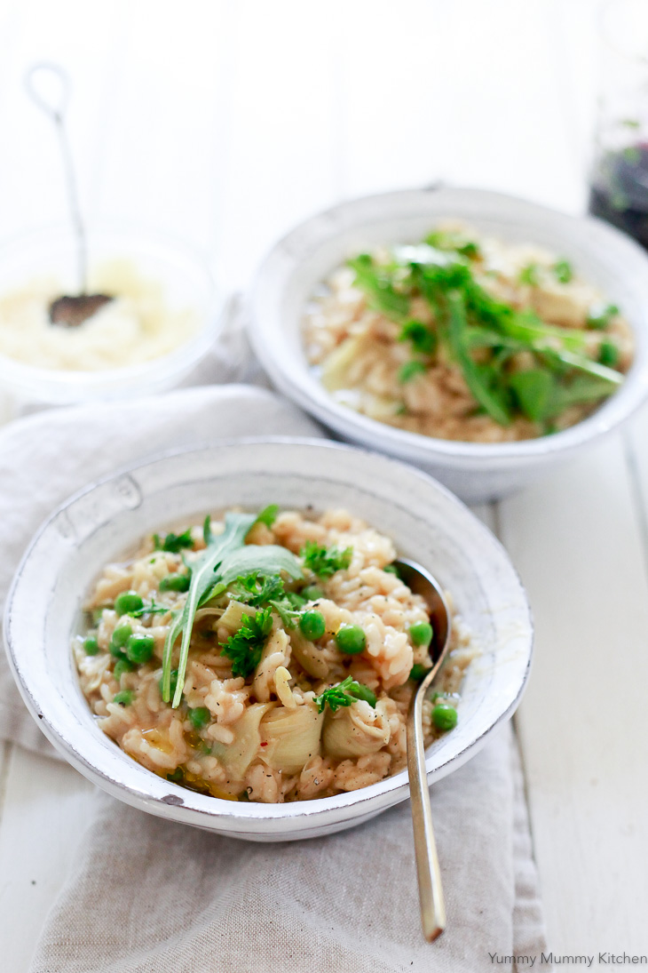 Beautiful rustic bowls of risotto with peas and artichoke hearts.