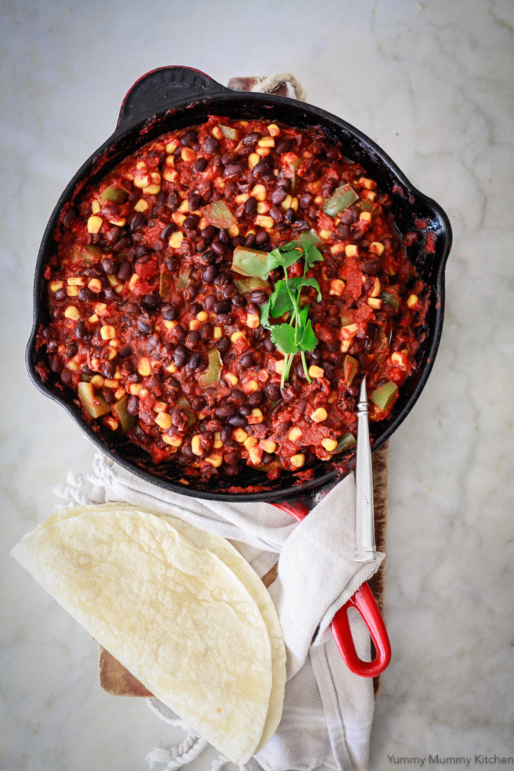 A skillet filled with black bean and corn enchilada filling to make vegetarian enchiladas.