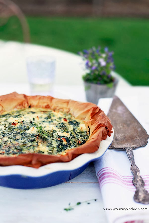 Quiche with spinach, feta, and a filo dough crust in a blue pie plate.