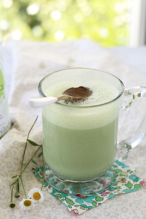A beautiful green matcha green tea latte in a clear mug. This vegan matcha latte recipe is made with almond milk and is a great cozy comforting drink.
