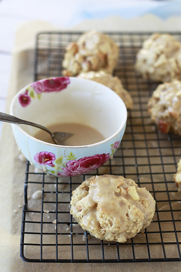 Oatmeal apple maple scones on a cooling wrack with a bowl of maple glaze.