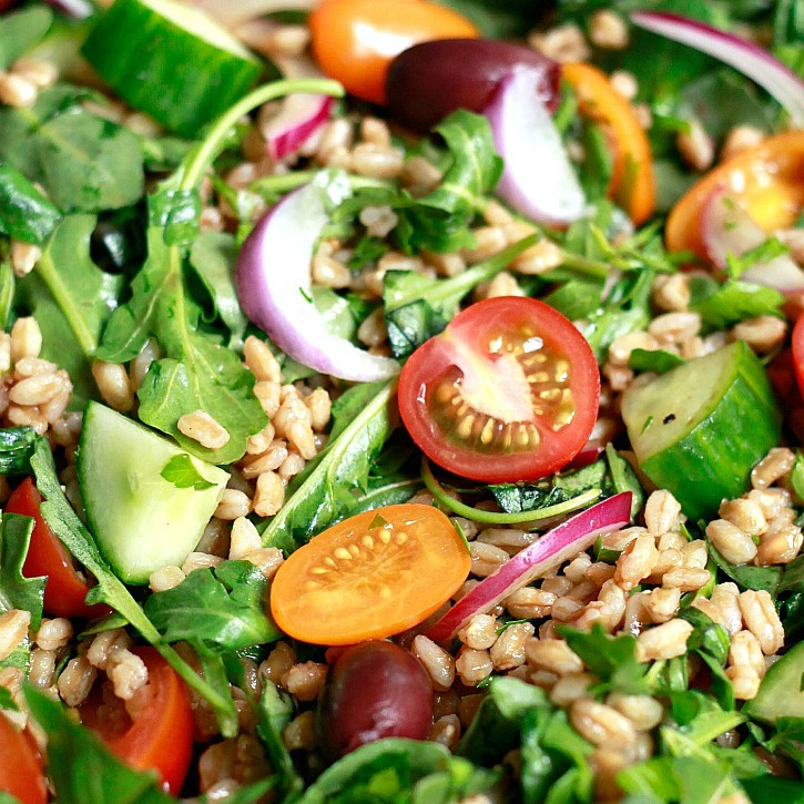 Italian farro salad with arugula, tomatoes, olives, and cucumber.