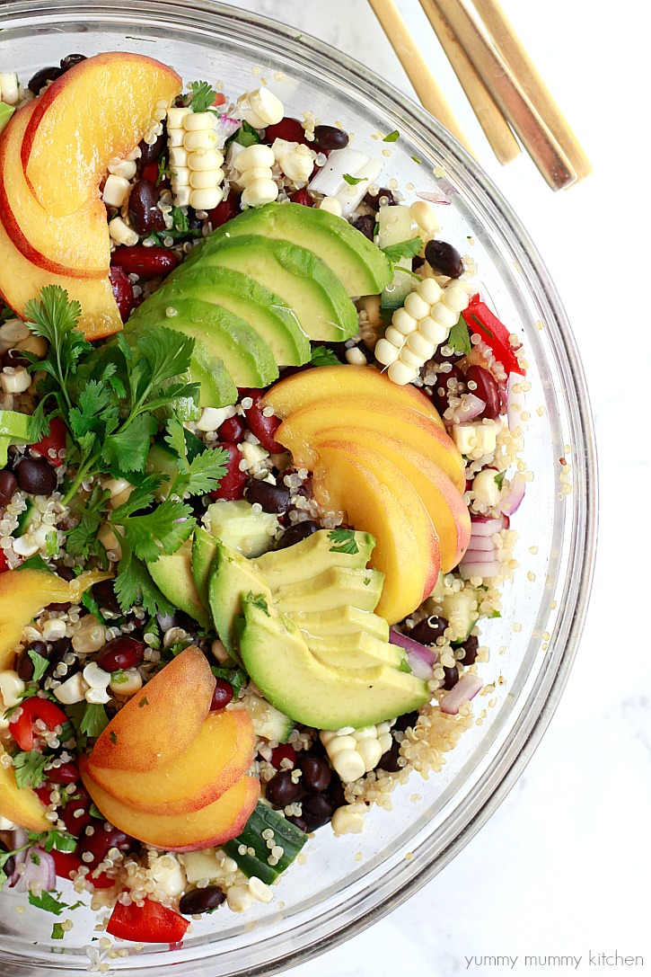 Quinoa salad with black beans, corn, bell pepper, avocado, and peaches. This beautiful vegan quinoa salad is perfect for summer parties or meal prep lunches at home.