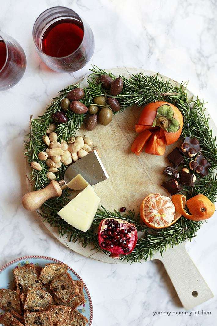 A beautiful holiday wreath cheese platter made with rosemary, cheese, marcona almonds, olives, persimmon, chocolate, citrus, and pomegranate. Served with red wine.