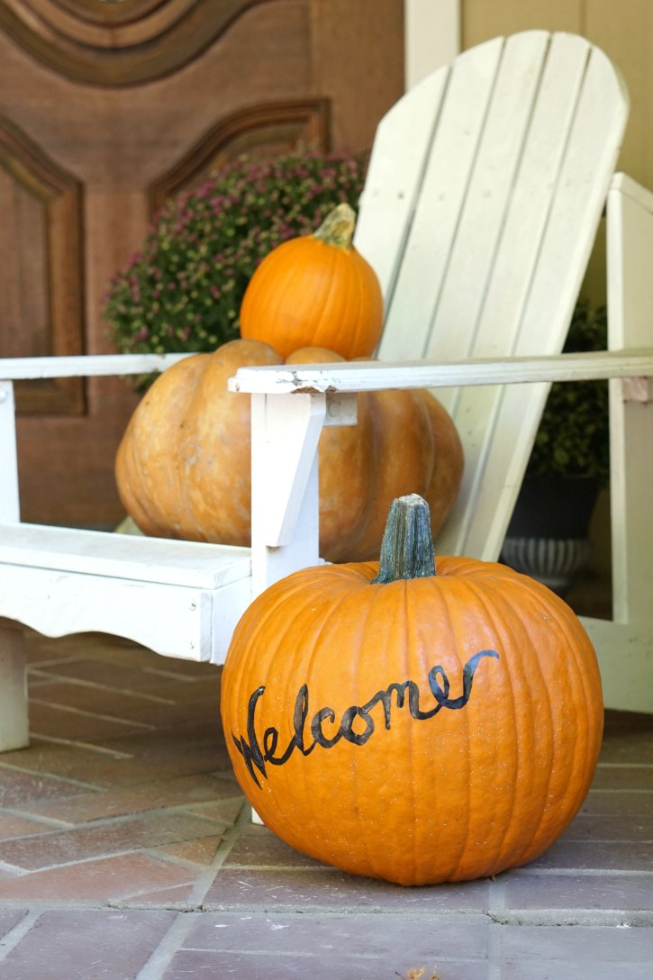 This welcome painted pumpkin is so cute as part of an autumn front porch.