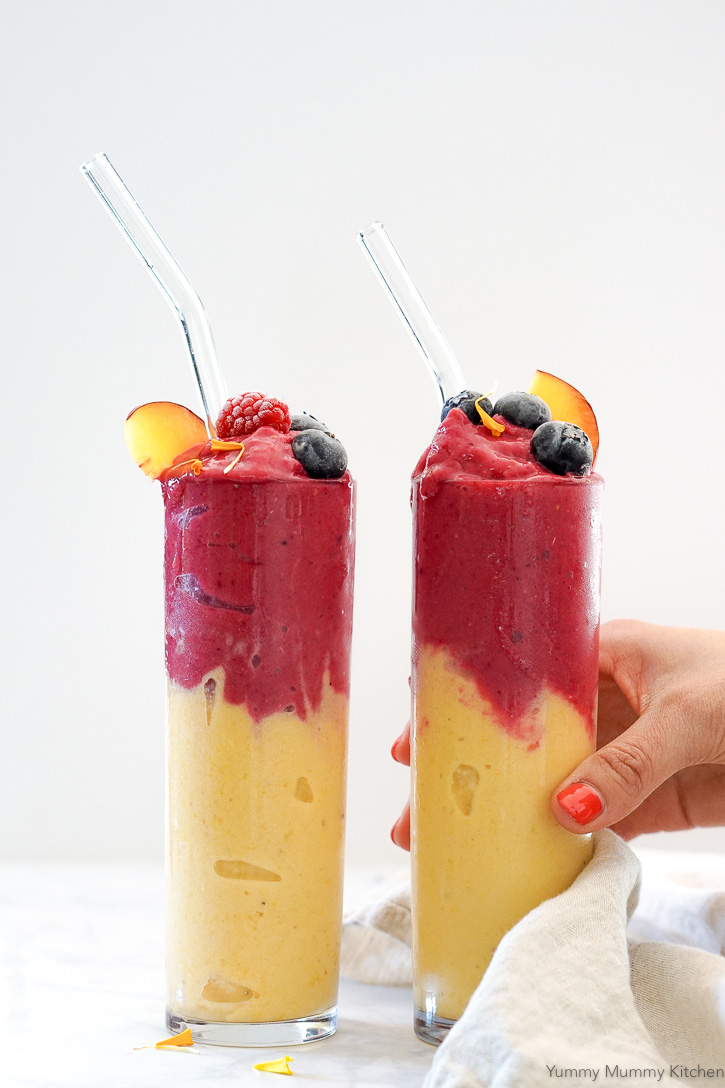 Beautiful peach smoothies topped with a pink raspberry layer in tall glasses. This easy vegan peach smoothie is so refreshing and delicious! It's perfect for breakfast or snack.