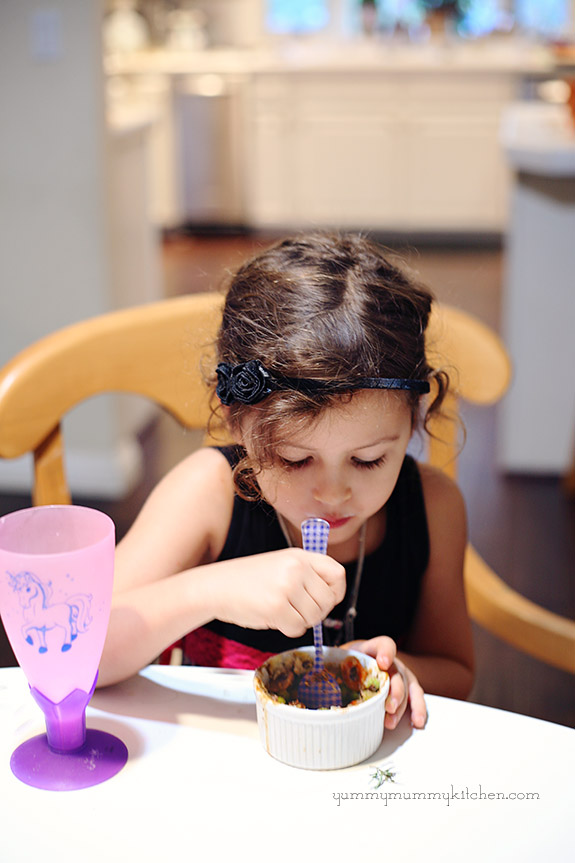 Girl eating an individual bowl of lentil shepherd's pie.