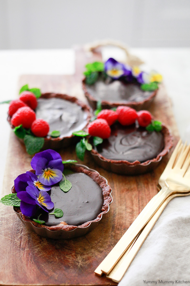 Beautiful chocolate tarts topped with edible flowers, raspberries, and mint leaves. These delicious tarts inspired by Hail Merry tarts are vegan, gluten free, and paleo friendly.